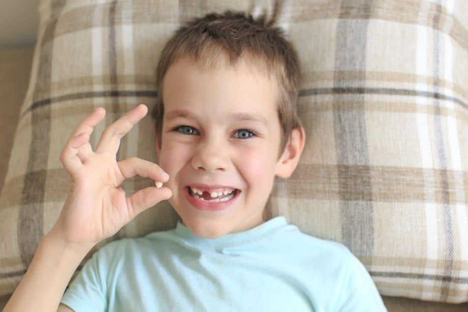A young boy lying in bed wearing a turquoise shirt is missing his front tooth & smiling while holding a tooth in his hand.